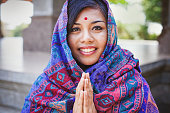 "Young women in colored headscarf keepung her hands in ""namaste"""