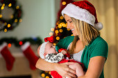 Beautiful new momther cradles baby girl at Christmastime