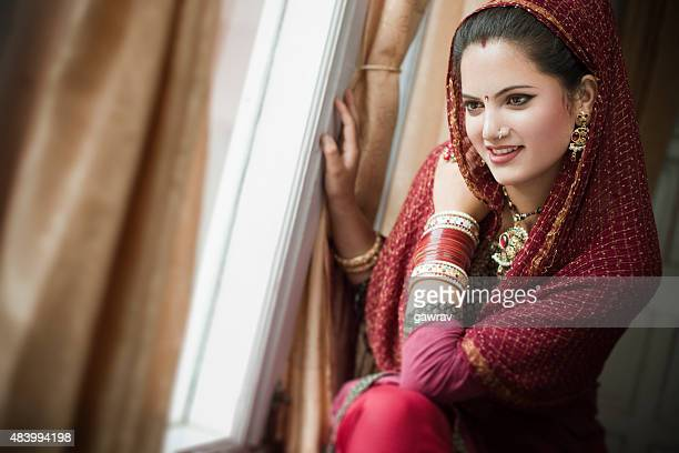 Beautiful newly married happy Indian young woman sitting near window.