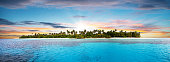 Beautiful nonsettled tropical island with perfect sunset sky and azure water with corals