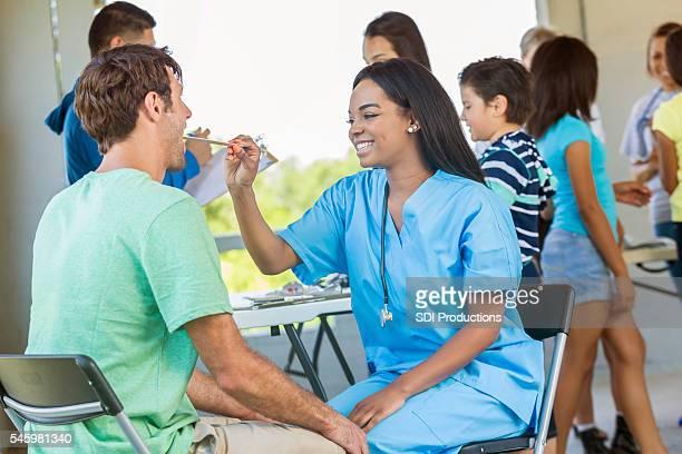 Beautiful nurse doing a health examination for a man