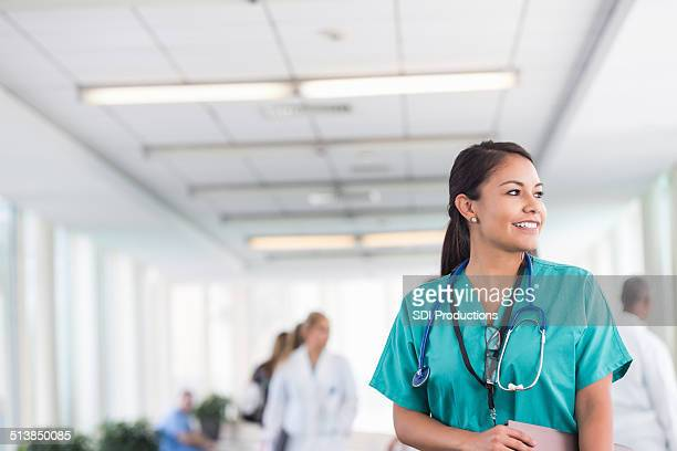 Beautiful nurse gazing out window during shift at hospital