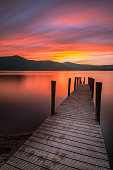A photograph of a beautiful orange sunset over Cat Bells in Keswick, the Lake District, England. The shot was taken on the Ashness Gate pier on the eastern side of Derwentwater Lake. A 10 stop ND filt