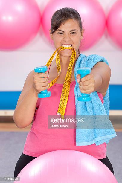 beautiful overweight woman doing pilates and biting measure tape
