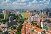 Beautiful panoramic aerial view of Chinatown district in Singapore. Red tiled roofs mong the modern buildings and skyscrapers. Cloudly weather.