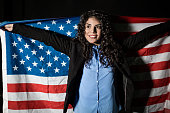 Beautiful patriotic young woman with the American flag . Isolated on black