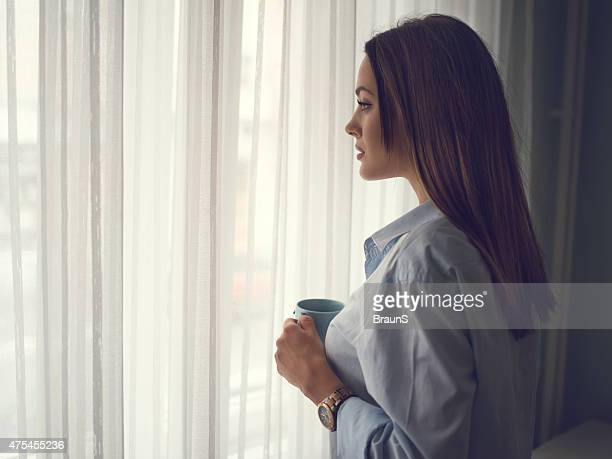 Beautiful pensive woman in a shirt by the window.