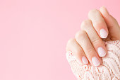 Beautiful, perfect, groomed woman's hand with light pink nails on the pastel background. Manicure, pedicure beauty salon concept. Empty place for text or logo.