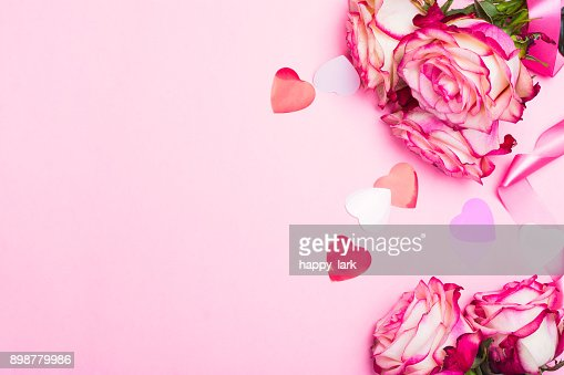 Beautiful pink rose, decorative confetti hearts and pink ribbon on pink Valentines day background : Stock Photo