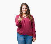 Beautiful plus size young woman over isolated background Beckoning come here gesture with hand inviting happy and smiling