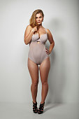 Full length image of beautiful plus-size woman in sexy lingerie and stilettos over grey background. Voluptuous woman posing proudly in body stocking.