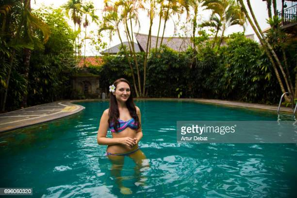 Beautiful portrait of a traveler girl in swimming pool with Bali flower in ear during travel vacations in Indonesia.