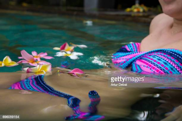 Beautiful portrait of a traveler girl in swimming pool with Bali flowers floating on water during travel vacations in Indonesia.