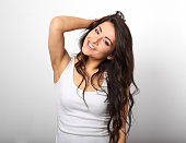 Beautiful positive fun happy woman in white shirt with toothy smile showing her epilation armpit on white background