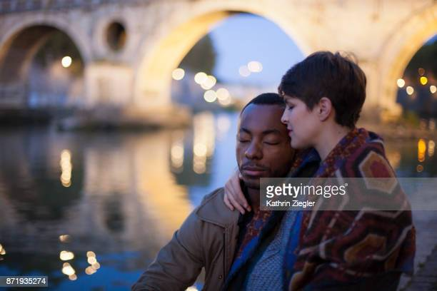 Beautiful pregnant couple embracing by Tiber River at the blue hour , Rome, Italy