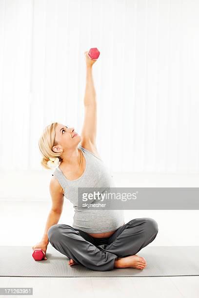 Schöne schwangere Frau, die Übungen.