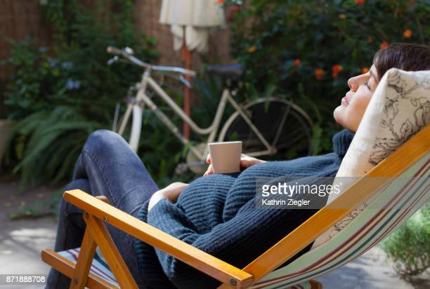 Beautiful pregnant woman relaxing on deck chair with a cup of tea
