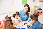 Portrait of a gorgeous Hispanic preschool teacher teaching her students in a classroom