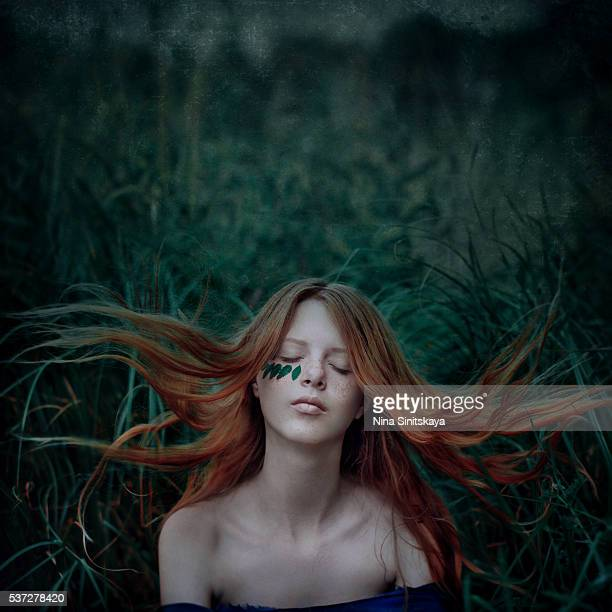 Beautiful red haired girl meditating with eyes closed sitting in the green grass and her hair blown by wind