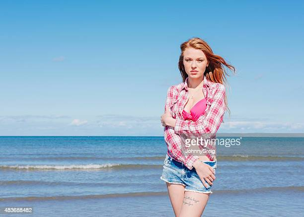 Beautiful red haired young woman standing by the sea