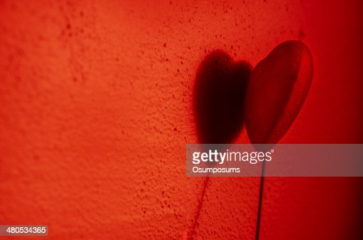Beautiful red heart play game with a shadow on wall : Stockfoto