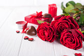 Beautiful red rose and dark chocolate for valentine day on white wooden background, copy space