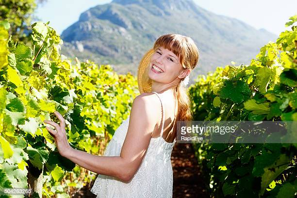 Beaux Cheveux roux dans les vignobles sourires par-dessus son épaule