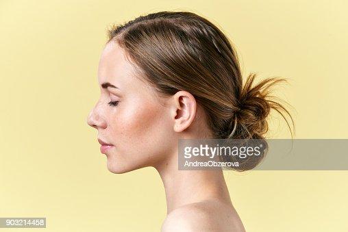 Schöne rothaarige Frau mit Sommersprossen Studioportrait Profil. Modell mit leichten nude Make-up, geschlossenen Augen, isoliert auf pastell gelb hinterlegt : Stock-Foto