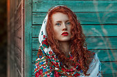 Redhead Woman Nature Portrait, in the  national head scarf. Long curved hair. Near the colorful wooden houses