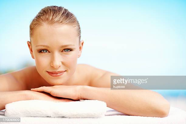 Beautiful relaxed woman lying on towel at spa