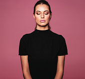 Portrait of caucasian female model standing with her eyes closed against pink background. Beauty portrait of beautiful relaxed woman with perfect skin and makeup.