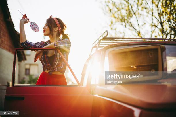 Beautiful retro style woman listening radio in the vintage car