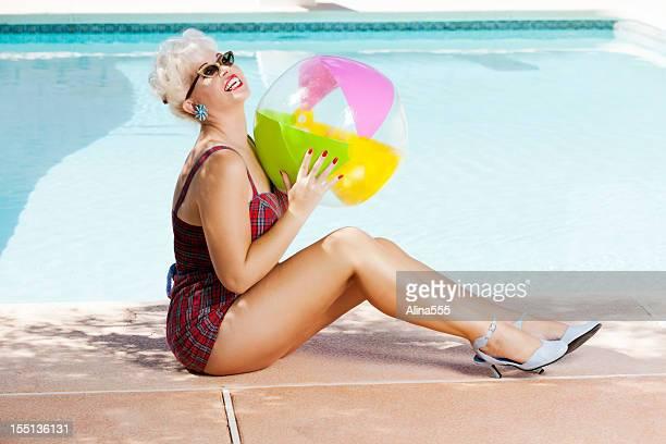 Beautiful retro woman enjoying sun by the pool