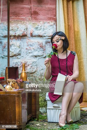 Beautiful retro woman smells red rose : Stock Photo