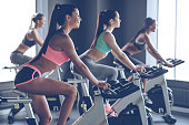 Side view of young beautiful women with perfect bodies in sportswear looking away with smile while cycling at gym