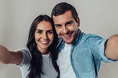 Beautiful romantic couple isolated on grey background. Attractive young woman and handsome man are making selfie, smiling and looking at camera.