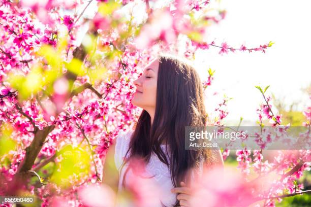 Beautiful russian girl posing between the nice blooming peach trees with pink colors during springtime in a warm day with sunny weather enjoying in the Catalonia countryside.