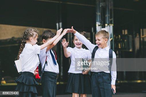 Beautiful school children active and happy on the background of school in uniform : Stock Photo