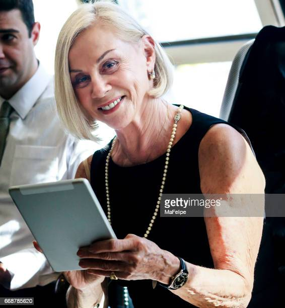 Beautiful senior businesswoman with tablet smiling to the camera.