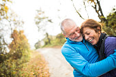 Beautiful active senior runners hugging outside in sunny autumn forest