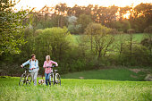 Beautiful senior couple outside in spring nature, walking with a dog and bicycles on grassland.