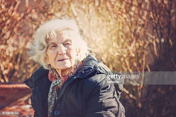 Beautiful Senior Woman Outdoors Lost in Thoughts
