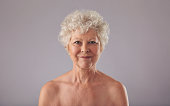 Portrait of beautiful senior woman shirtless against grey background. Naked old woman smiling at camera.
