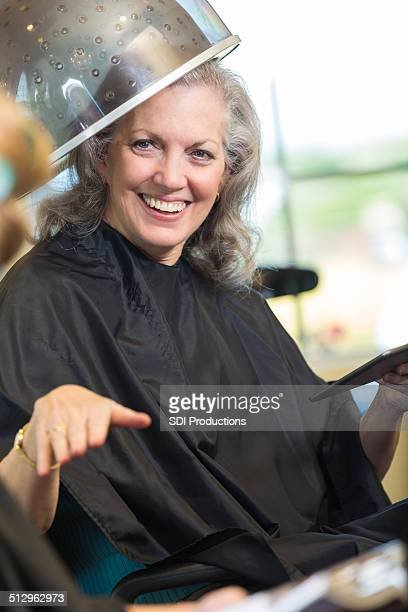 Beautiful senior woman sitting under hairdryer in beauty salon