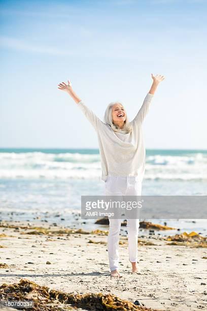 Beautiful senior woman with arms raised