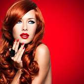 Beautiful sensual woman with long red hairs and red nails on red background