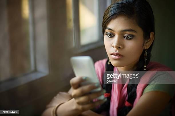 Schöne ruhige indische Mädchen lesen SMS-Sitzbereich in der Nähe der Fenster.