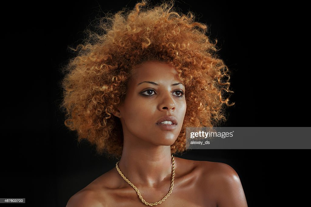 Beautiful serious African woman on black background