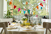 Beautiful served round table with decorations in dining room. Little yellow bunny, willow branches decorated with colorful Easter eggs. Spring holiday setting.