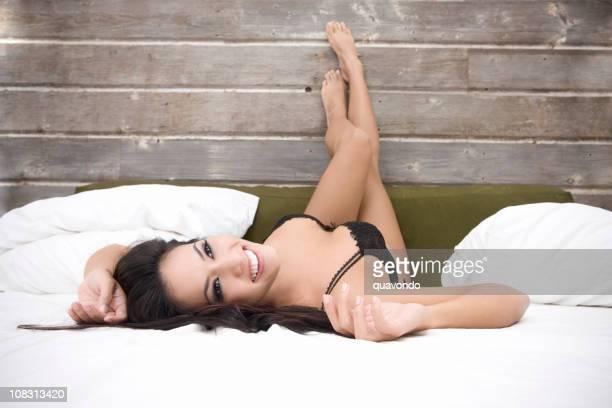 Schöne Sexy Brunette Junge Frau in Dessous auf dem Bett, Copyspace